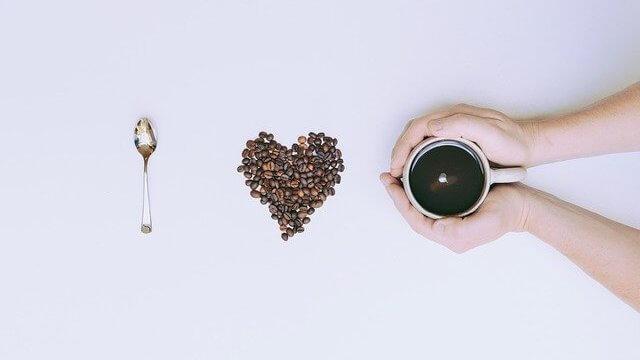 コーヒーカップで手を温める写真